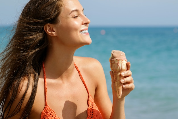 Woman with cone of ice cream on the beach
