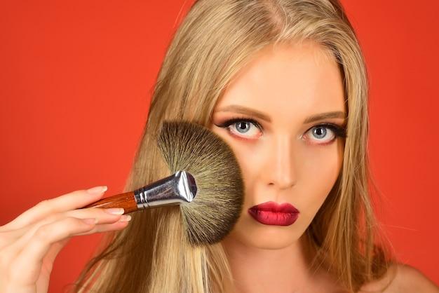化粧ブラシを持つ女性。メイクアップの女性ファッションモデル。美しい顔、完璧な肌。スキンケア。