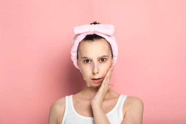 Женщина с косметической маской на лице с удивлением открывает рот и трогает рукой лицо на розовом пространстве