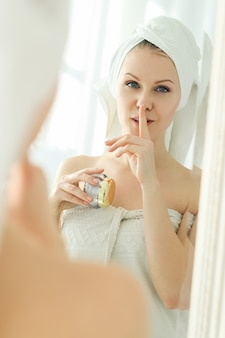 Woman with cosmetic products and towel on her head after shower