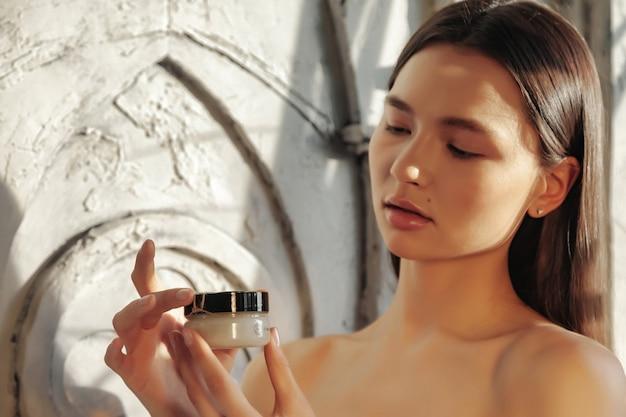 顔の肌に塗る化粧クリームの女性。女性は葉から日陰で古い壁の背景にクリームを保持します。健康的なライフスタイルとセルフケアの広告コンセプト。 spaのコピースペース