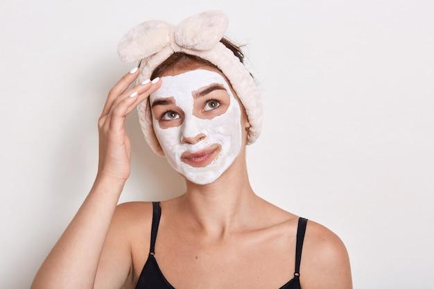 Женщина с нанесенной косметической маской, глядя вверх и касаясь ее брови, с задумчивым выражением лица, делая косметические процедуры дома, стоит на белом фоне.