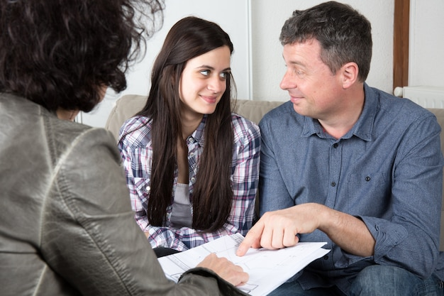 Woman with couple on sofa, blue prints for new house