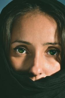 カメラを見ている緑色の目で覆われた顔を持つ女性