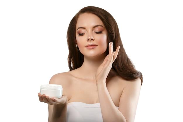 クリーム色の顔のスキンケアのコンセプトを持つ女性、健康的で清潔な新鮮な顔の肌のクローズアップ、手にクリームを持った女性モデル。スタジオショット。