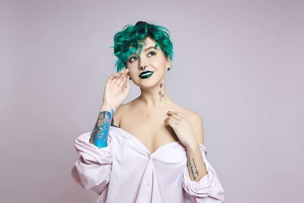 Woman with creative green coloring hair and makeup, toxic strands of hair. bright color curly hair on the girl head, professional makeup. woman with tattoo