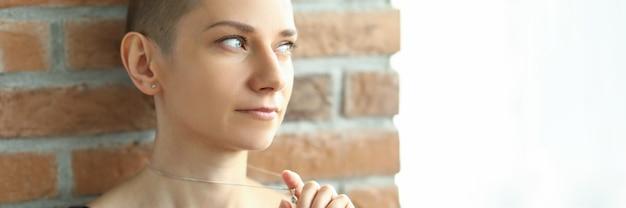 Женщина с креативной прической смотрит в окно, стоя у кирпичной стены