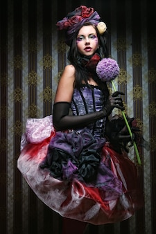 Woman with creative make-up in doll style with flower