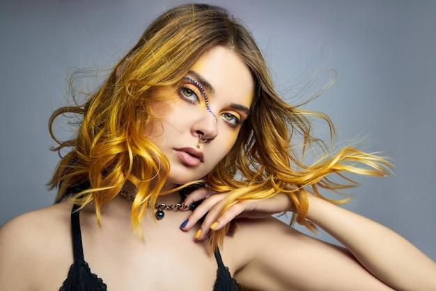 Женщина с творческой желтой окраской волос и макияжем со стразами, фиолетовыми прядями волос второго слоя. яркие вьющиеся волосы на голове девушки, профессиональный макияж