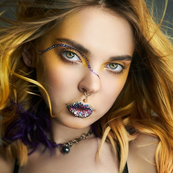 Woman with creative yellow coloring hair and makeup with rhinestones, purple strands of hair second layer. bright color curly hair on the girl's head, professional makeup