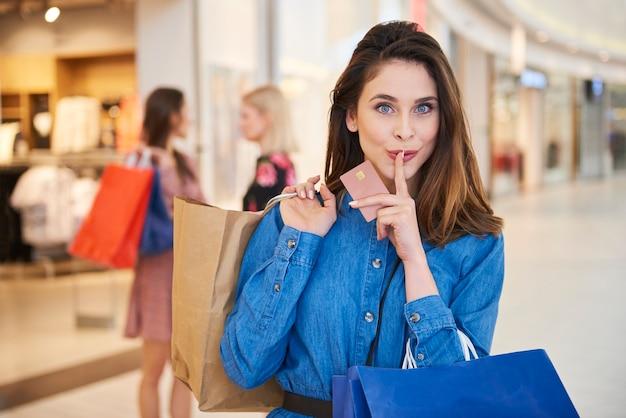 クレジットカードと完全な買い物袋を持つ女性