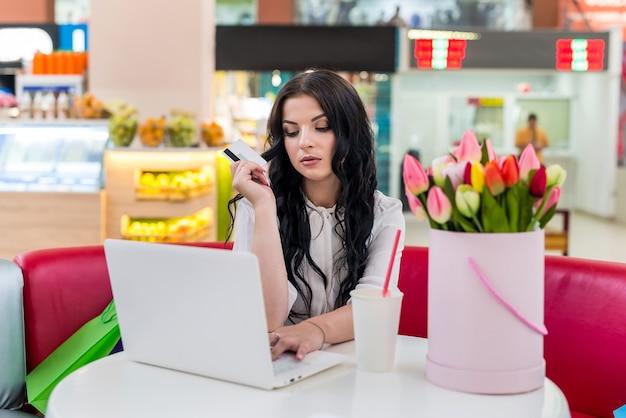 ショッピングをしているカフェでクレジットカードとラップトップを持つ女性