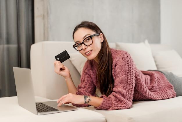 クレジットカードと自宅のソファの上のラップトップを持つ女性