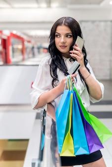 Женщина с кредитной картой и хозяйственными сумками разговаривает по телефону
