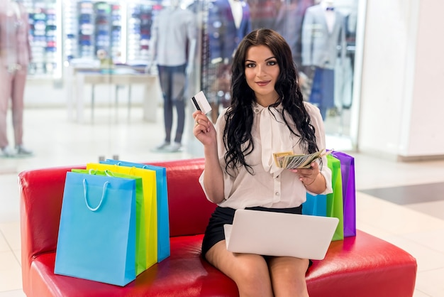 Woman with credit card, dollars and laptop in mall