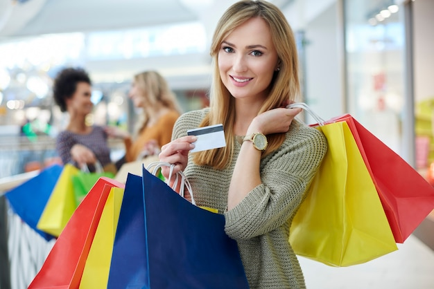 Donna con carta di credito e borse della spesa piene
