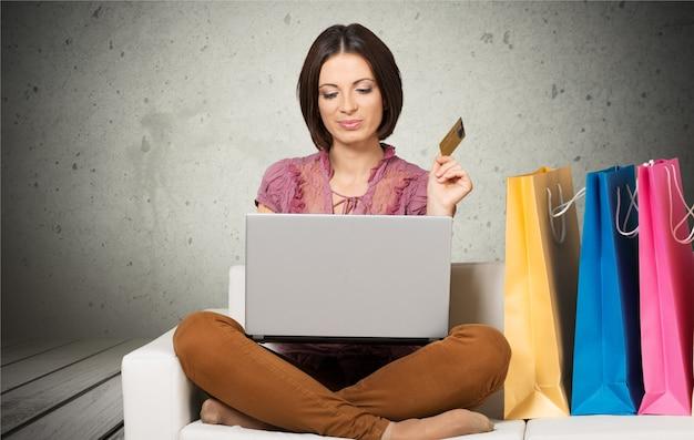 신용 카드 노트북을 가진 여자입니다. 노트북, 전자 상거래 개념을 사용하여 인터넷에서 온라인 쇼핑
