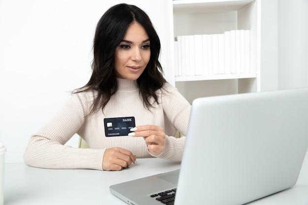 Женщина с кредитной картой, делая платежи онлайн, сидя в изолированном офисе.