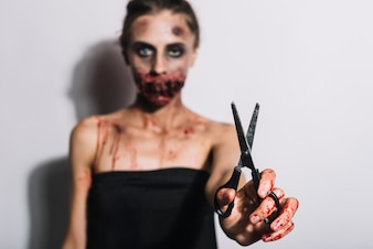 Woman with creepy grime holding scissors