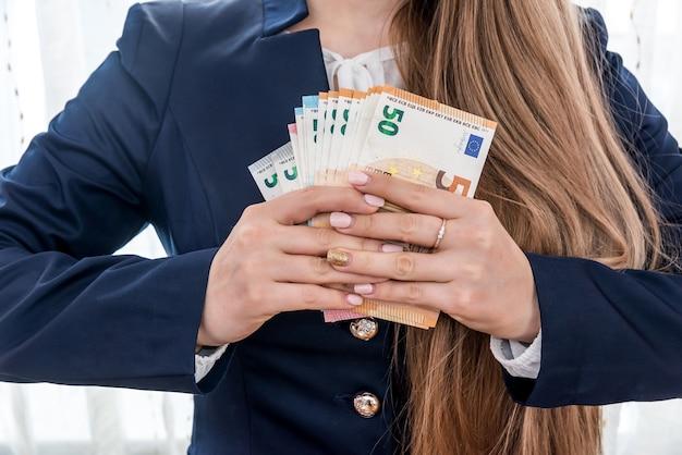 유로 지폐를 보여주는 교차 손가락을 가진 여자
