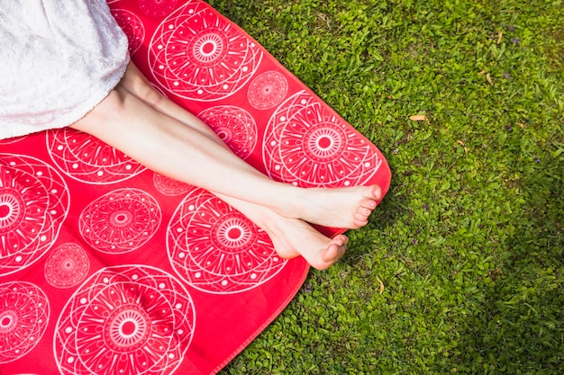 Woman with crossed legs sitting on red blanket over the green grass