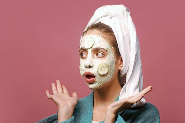놀란 된 얼굴에 오이 마스크를 가진 여자입니다. 회춘, 건강, 젊음. 뷰티 살롱 개념. 피부 및 모발 관리, 스파, 웰빙. 머리에 목욕 타월로 소녀입니다.