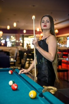 Woman with cue posing in billiard pub