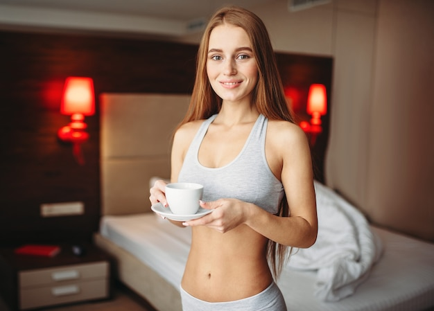 Woman with cup of coffee in hands, bedroom
