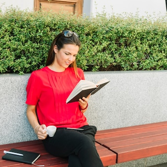 Woman with cup of coffee reading book