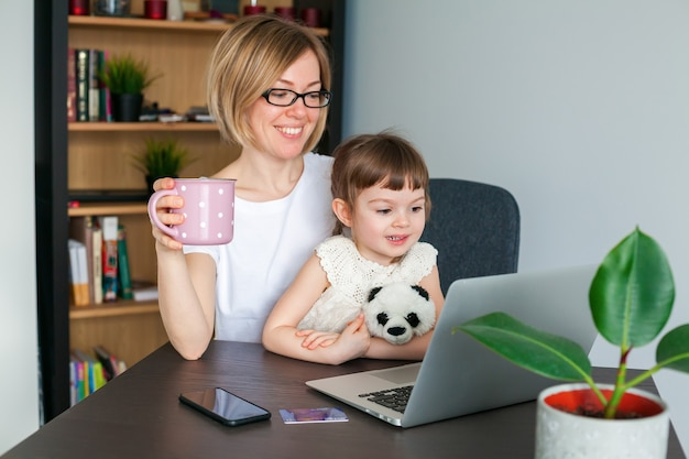Woman with a cup and her little daughter watching something on a laptop at home
