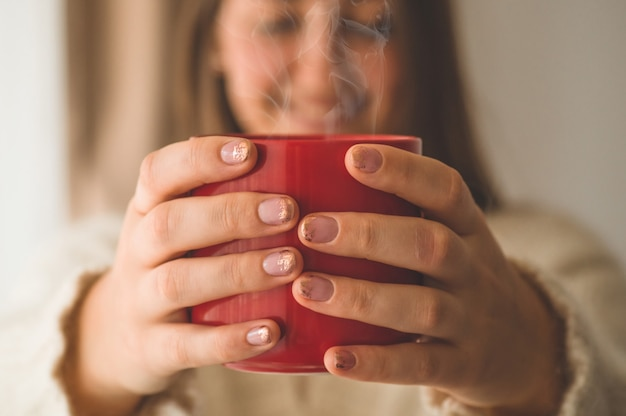 Woman with cup of hot drink by the window. good morning with tea. autumn winter time