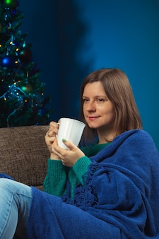 Woman with cup of a hot drink on the couch on christmas eve alone how to stay at home to save lives