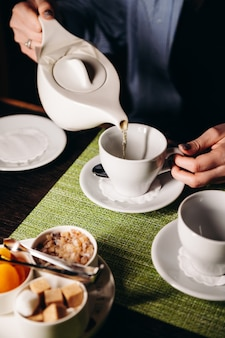 A woman with a cup of hot tea in her hands sits in the restaurant the girl drinks aromatic tea enjoy the moment take a break