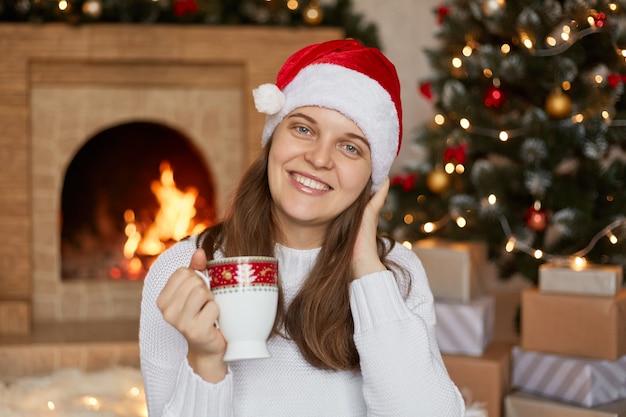 暖炉のそばのリビングルームに座って、こぼれるような笑顔で、居心地の良い雰囲気の中で温かい飲み物を楽しんでいる、クリスマスツリーとプレゼントボックスの近くでポーズをとっている女の子。