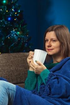 크리스마스 이브에 혼자 소파에 뜨거운 음료를 한 잔 든 여자 생명을 구하기 위해 집에 머무르는 방법