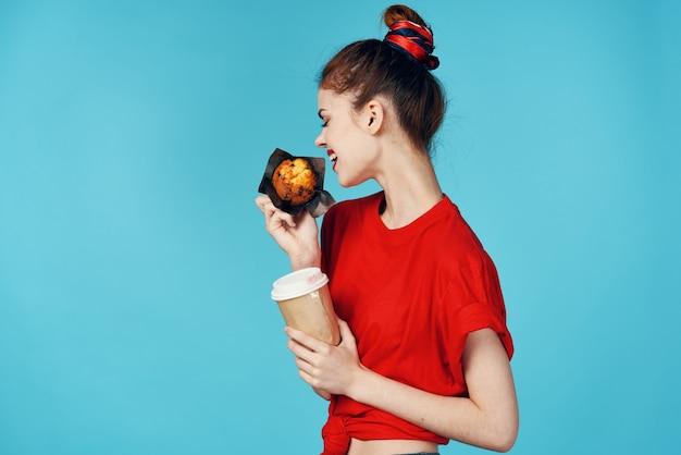 手にコーヒーとカップケーキのカップを持っている女性朝食ダイエット食品