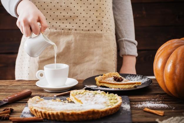 커피와 호박 파이의 컵을 가진 여자
