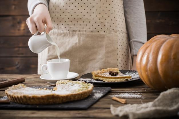 Женщина с чашкой кофе и тыквенным пирогом