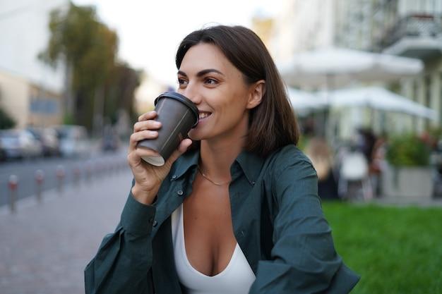 Женщина с чашкой кофе на улице на городской улице на закате, счастливая улыбка, наслаждаясь летними днями