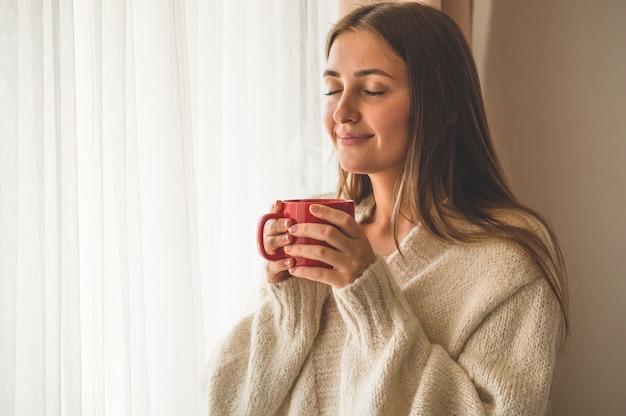 창이 뜨거운 음료 한잔과 함께 여자. 차와 함께 좋은 아침. 가을 겨울 시간