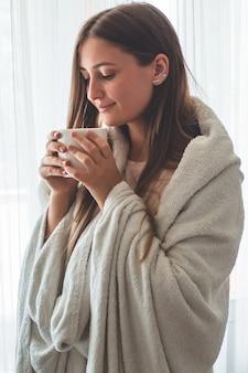 창이 뜨거운 음료 한잔과 함께 여자. 창문을보고 차를 마신다. 차와 함께 좋은 아침. 가을 겨울 시간