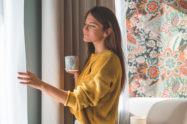 窓際に温かい飲み物のカップを持つ女性。窓を見てお茶を飲む。おはようお茶で。秋冬時間