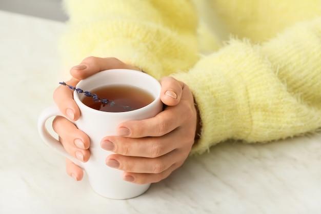 Женщина с чашкой горячего чая за столом, крупным планом