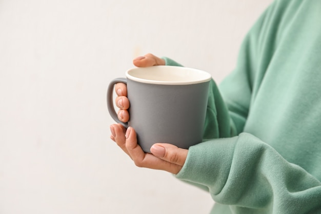 明るい表面に熱いお茶のカップを持つ女性