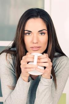 家でお茶を飲む女性
