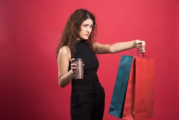 Donna con la tazza che mostra i suoi due sacchi di vestiti nuovi su sfondo rosso
