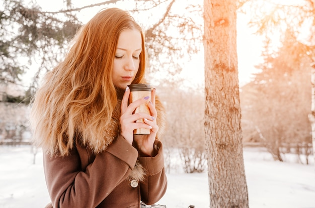 Woman with cup of tea or coffee in the winter park