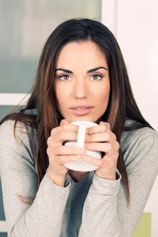 Woman with cup of tea at home
