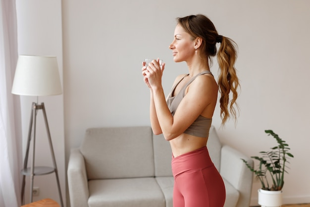 Woman with a cup of water after a workout at home in the living room