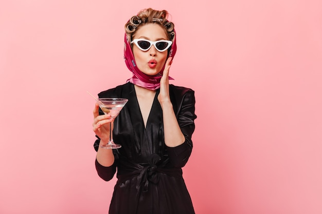 Woman with curlers in surprise poses on pink wall